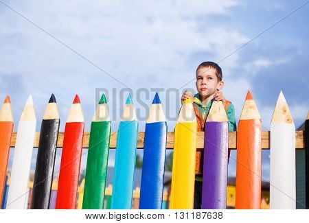 boy dreams of standing behind the fence of pencils. the concept of accessible education for children. copy space for your text
