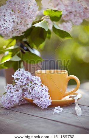Bouquet of a lilac and orange cup with a spoon on a wooden table.