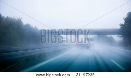 Highway traffic on a rainy day on German European autobahn with cars driving over 200 kmh