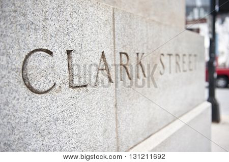 Name of Clark Street carved on a concrete stone wall at Clark street for people's convenience in Chicago, Illinois. The color of the wall in the picture is white.