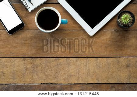 Office desk table with blank screen tablet blank screen smarphone notebok pen and coffee cup .Top view with copy space