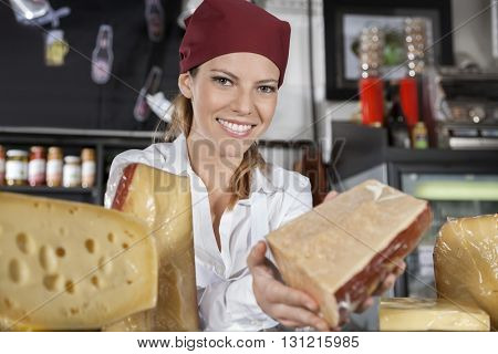 Saleswoman Showing Cheese In Grocery Shop