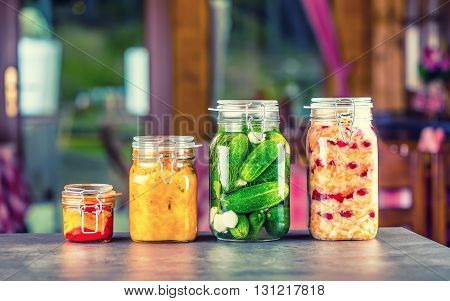 Preserving. Pickles jars. Jars with pickles pumpkin dip white cabbage roasted red yellow pepper. Pickled Vegetables. Vegetable being prepared for preserving. Toned image.