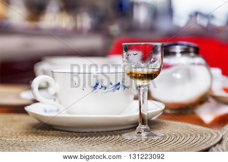 Close view small glass calyx with alcoholic drink on feast table