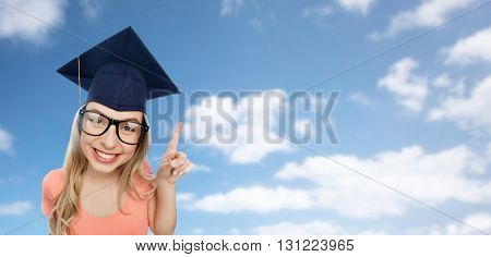 people, graduation and education concept - smiling young student woman in mortarboard and eyeglasses pointing finger up over blue sky and clouds background