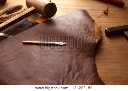 Leather craftmans work desk . Piece of hide and lacing hole punch on a work table.
