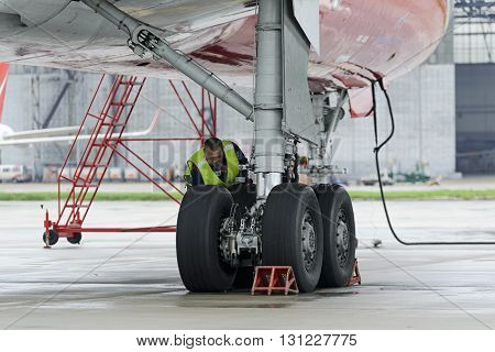 MOSCOW, RUSSIA - MAY 19, 2016: Aircraft  Tupolev-204 Red Wings airline in the parking lot of the international airport Domodedovo. The service engineer carry out work on inspection of the landing gear.