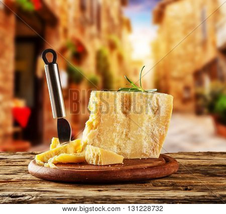 Parmesan cheese on cutting board placed on wood, blur old street on background
