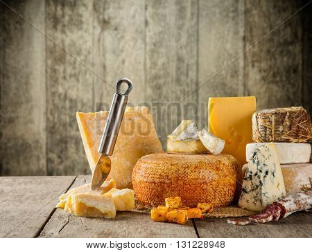 Various types of cheese placed on wooden table, copyspace for text. Wooden planks on background