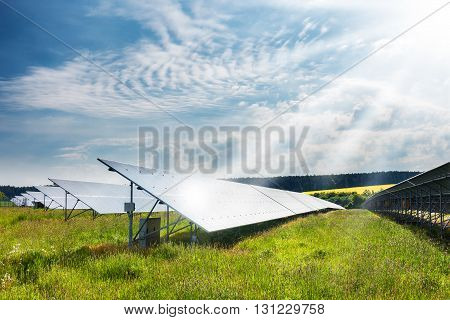 Landscape with solar power plant. Solar panels in sunny summer countryside under sun rays and blue sky. Solar power generation. Czech Republic Europe