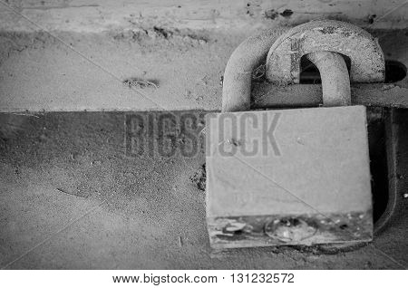 Old padlock on metal door in black and white