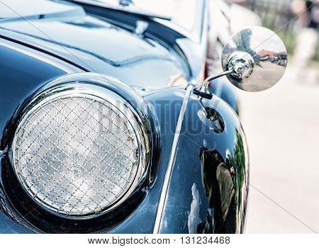Shiny blue vintage car. Detail view of the headlight. Retro car. Front light. Retro automobile scene. Circle headlamp. poster