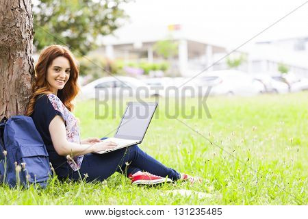 Happy student girl sitting on the grass and using laptop computer