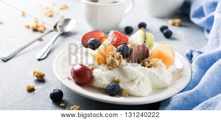 Healthy breakfast, quark with granola, fruits and berries on light wooden background.