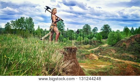 Beautiful athletic woman in the image of an ancient barbarian warrior on a high cliff looking into the distance on summer nature background.