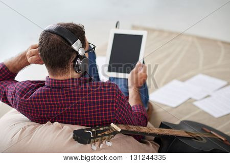 Young man listening to the song her wrote on tablet computer