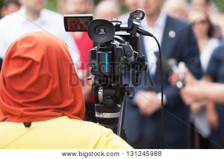 Filming an event with a video camera. Press conference.