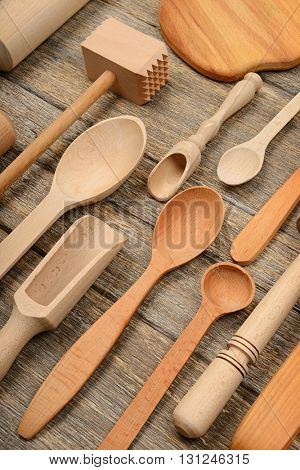 Set wooden kitchen utensils on wooden table. Spoon, fork, rolling pin, hammer kitchen, kitchen spatula. Top view.