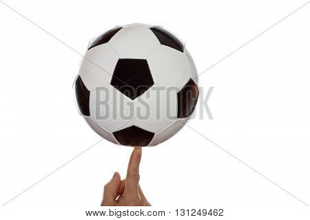 a man is balancing a soccer ball on finger