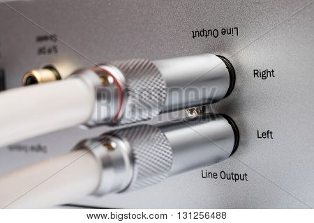 Sockets and plugs of the line output on an aluminum panel. It is a part of the rear panel of CD or DVD player.
