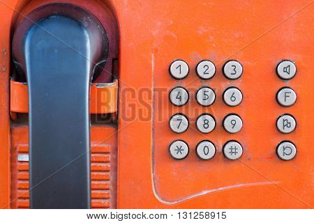 fragment or part of the old payphone of red color and with a push button set of number closeup