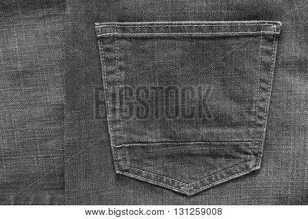 fragment of trousers from jeans material or jeans clothes with the big sewn pocket closeup for the textile textured background of black color