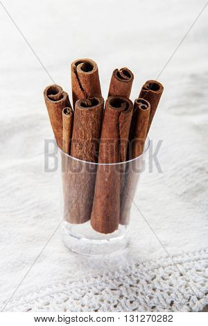 cinnamon in the glass close up on white