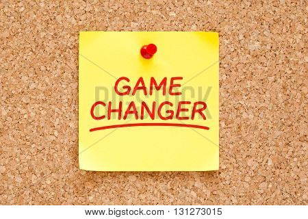 Game Changer written on yellow sticky note with red marker pinned on cork board.