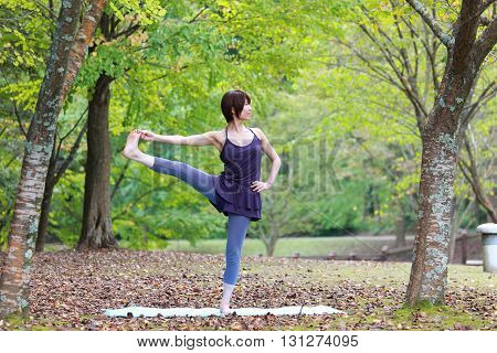 Japanese woman outside doing yoga Extended Hand-To-Big-Toe Pose poster