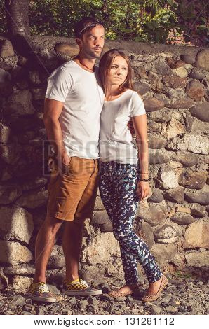 Young Beautiful Stylish Couple Sitting Near Big Stone Wall