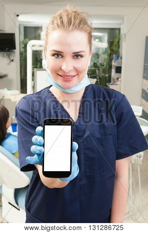 Young attractive dentist holding a smarthphone with blank screen with copyspace in dental office