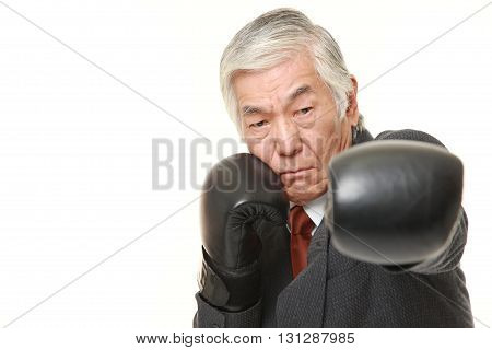 portrait of senior Japanese businessman throwing a left jab on white background