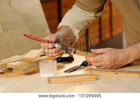 Carpenter at work gluing piece of wood closeup