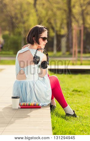 Female Posing Outside In Park With Headphones, Books And Coffee