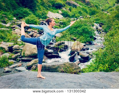 Vintage retro effect hipster style image of woman doing yoga asana Natarajasana - Lord of the dance pose outdoors at waterfall in Himalayas