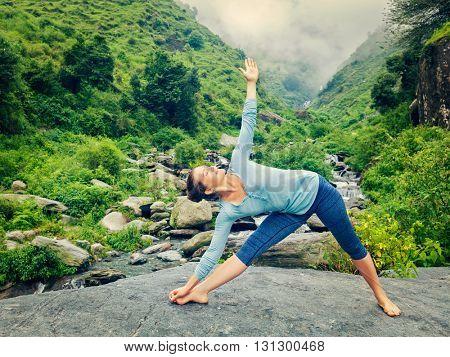 Vintage retro effect hipster style image of woman doing Ashtanga Vinyasa yoga asana Utthita trikonasana - extended triangle pose outdoors at waterfall in Himalayas