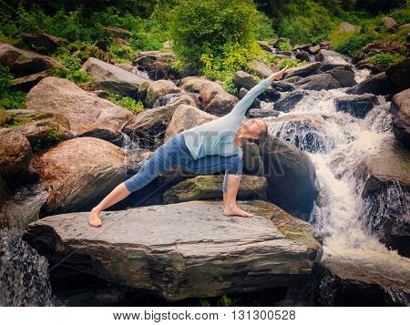 Vintage retro effect hipster style image of fit woman practices yoga asana Utthita Parsvakonasana -  extended side angle pose outdoors at water