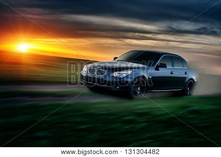 Saratov, Russia - April 30, 2013: Car BMW E60 drive at countryside road at sunset