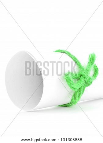 Handmade green string knot tied on white message tube isolated