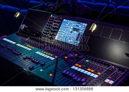 Large modern show sound controller with lighted screens and ajusted presets - close up photo