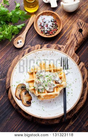 Savory waffles with corn and mushroom creamy sauce on a plate on a wooden background Top view