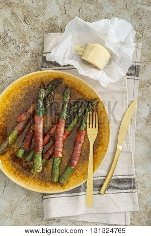 Purple asparagus wrapped with gammon on a plate