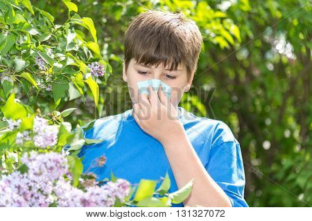 Teen boy with allergic rhinitis near blossoming lilac