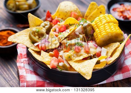 Nachos with melted cheese sauce, salsa and corn cobs in bowl on brown wooden background Top view