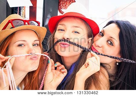 Playful girlfriends funny faces selfie with fake mustache at street market - Beautiful girls having fun during shopping day in old town - Concept of carefree youth - Main focus on middle subject
