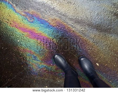 High angle shot of rain boots on big oil spill