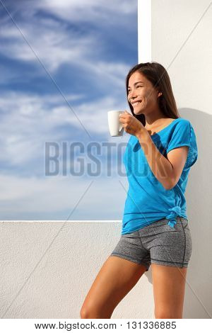 Morning coffee breakfast yoga woman in activewear at home outdoor terrace living. Asian fitness fit girl drinking enjoying summer sun outside after exercise workout. Healthy active lifestyle.