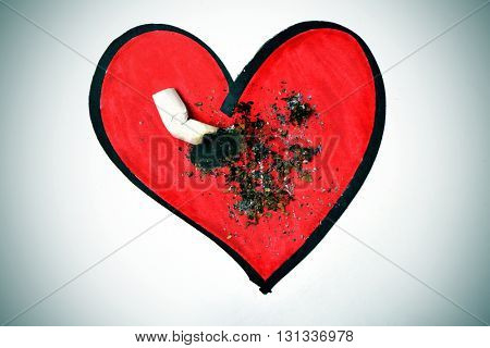 a cigarette butt put out on a drawing of a red heart, with a dramatic effect