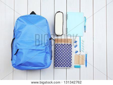 Backpack and school supplies on wooden background, close up. Top view.