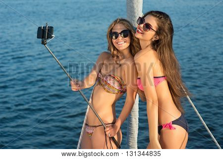 Girls with selfie stick smiling. Ladies on yacht taking selfies. Capturing the funniest moments. Carelessness and joy.